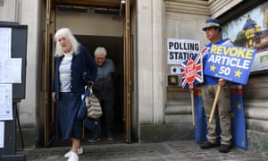 Voters exit a polling station while activist and remain protester Steve Bray campaigns in London.