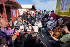 Gypsies sing and play guitar between their folklore wagons