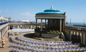 Striped deck-chairs in a semi circle around the bandstand on the promenade at Eastbourne in Sussex