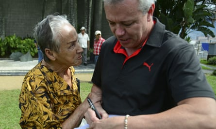 """John Jairo Velasquez, A.K.A """"Popeye"""", signs a bank note for a woman beside the tomb of Colombian drug lord Pablo Escobar."""