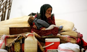 Syrian woman carries her child at a temporary refugee camp