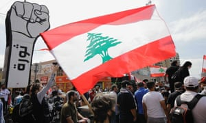 A protester waves a Lebanese flag as demonstrators from across Lebanon gather against dwindling economic conditions in the country, at al-Nour Square in the centre of the northern port city of Tripoli on 3 May 2020.