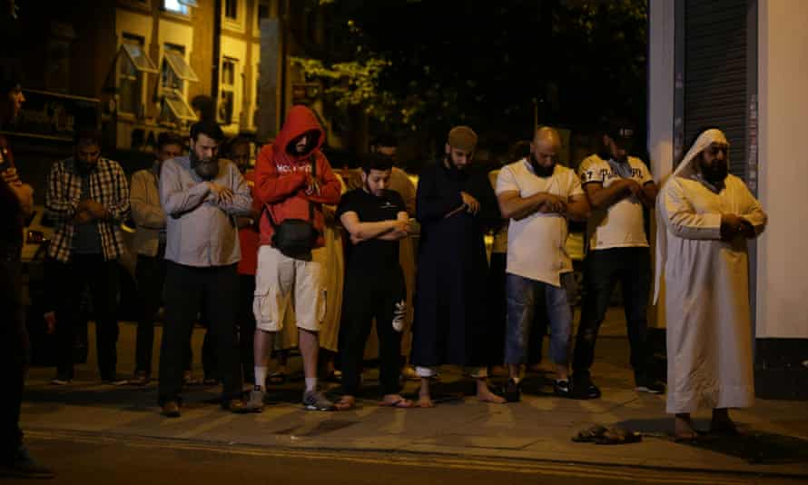 A group of people praying on the pavement in Finsbury Park after the van attack last year.