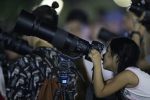 A girl looks through the viewfinder of a camera to see a lunar eclipse in Manila, Philippines