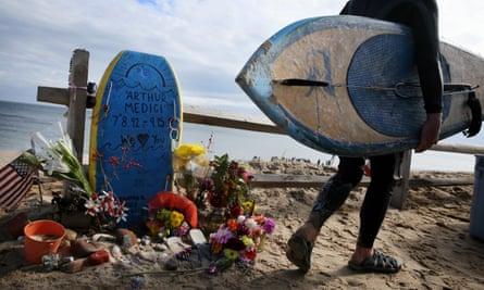 A surfer passes passes a makeshift memorial for Arthur Gava Medici at Newcomb Hollow Beach in Wellfleet, Massachusetts.