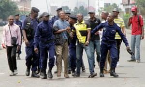 Congolese policemen detain opposition activists in Kinshasa.
