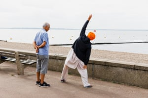 A  man watches a Sikh man exercise