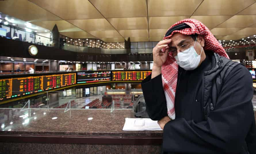 A trader wearing a protective mask follows the market at the Boursa Kuwait stock exchange in Kuwait City.