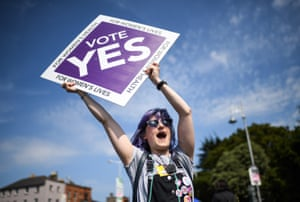 Members of the public hold yes placards on Fairview road in Dublin, Ireland.