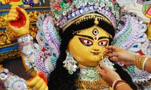 A Hindu devotee decorates a Durga idol with gold ornaments
