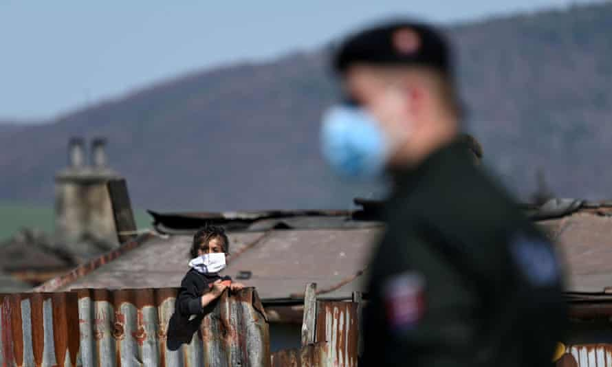 A police officer patrols outside a Roma settlement in Krompachy, Slovakia