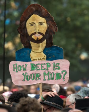 "A fan holds up a ""How deep is you mud?"" banner during Barry Gibb's set at Glastonbury"