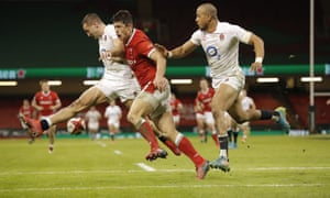 Jonny May of England and Louis Rees-Zammit of Wales challenge each other over the ball.