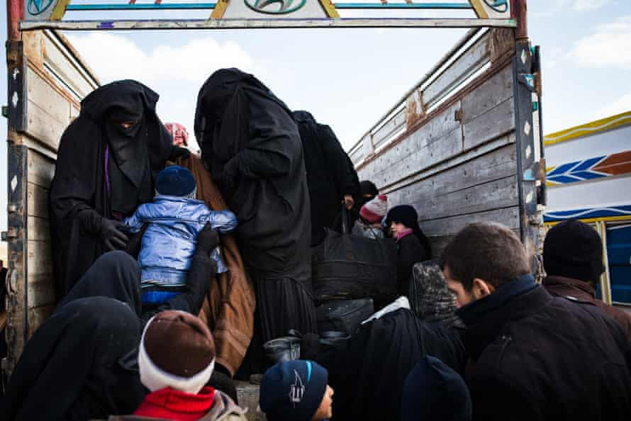 Women and children, believed to be isis families, climb on the back of truck at a civilian screening point on the outskirts of Baghuz, 9 February 2019.