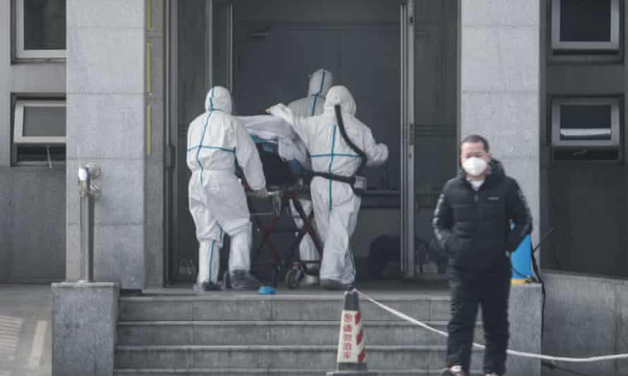 Medical staff carry a patient into a hospital in Wuhan where patients infected with the coronavirus are being treated.