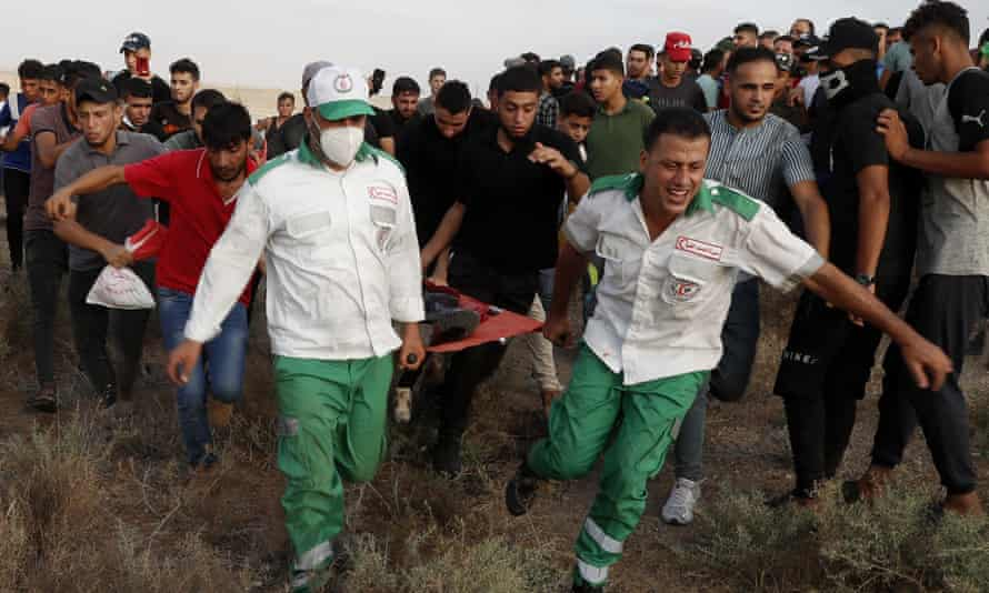 Medics evacuate a wounded person from the fence of the Gaza Strip border with Israel on 21 August.