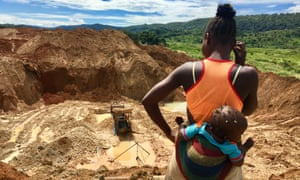 A woman with a baby stares into an abandoned gold mine