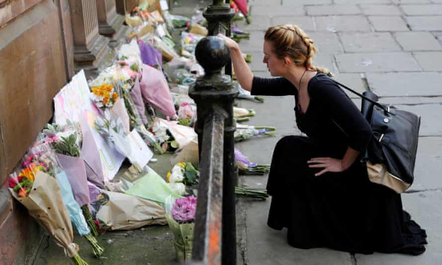 A woman lays flowers for the victims of the Manchester Arena attack, in central Manchester, Britain May 23, 2017. REUTERS/Darren Staples