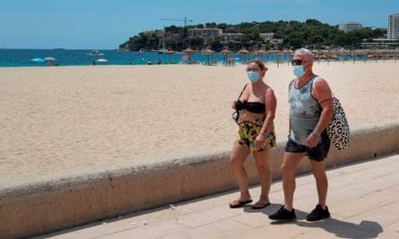 Tourists walk at Magaluf beach, Calvia, in Majorca.