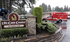 An ambulance backs into a parking lot, 6 March 2020, at the Life Care Center in Kirkland, Washington.