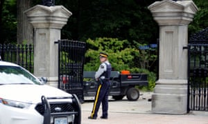 A police officer outside Rideau Hall in Ottawa after an armed man drove his truck through the gates.