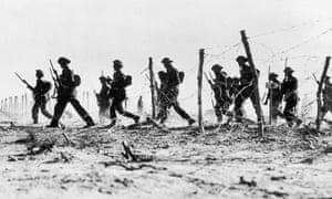 British infantry making their way through a gap in barbed wire defences during the advance on Tobruk.
