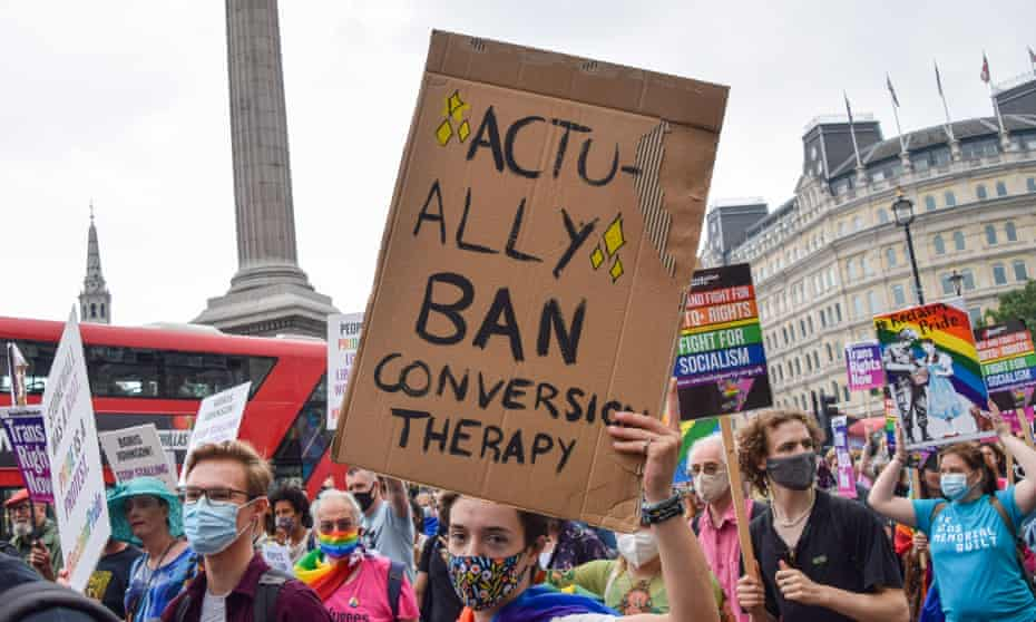 A demonstrator holds a placard that says Actually Ban Conversion Therapy in Trafalgar Square during the Reclaim Pride protest.