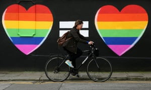 A woman cycles past a marriage equality mural