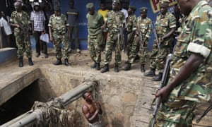 A suspected member of the ruling party's Imbonerakure youth militia pleads with soldiers to protect him from demonstrators in Bujumbura, Burundi, May 2015