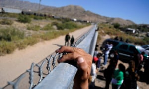 A person holds onto the fence marking the border between the US and Mexico in Juárez.
