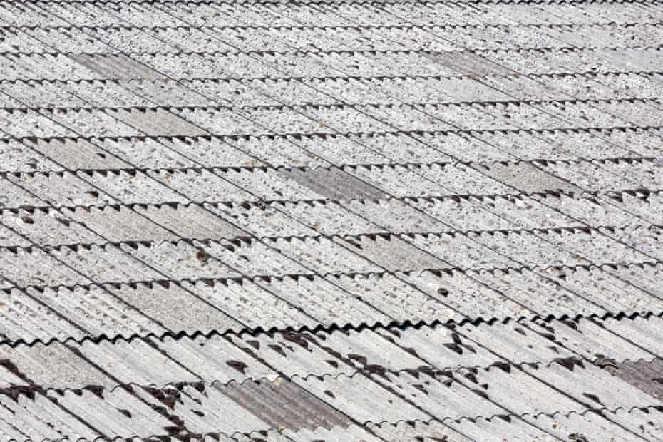 Surface of an old large corrugated asbestos cement or AC sheet or Fibro sheeted roof