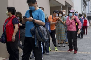 People queue up outside a vaccination center for BioNTech in Hong Kong earlier this week.