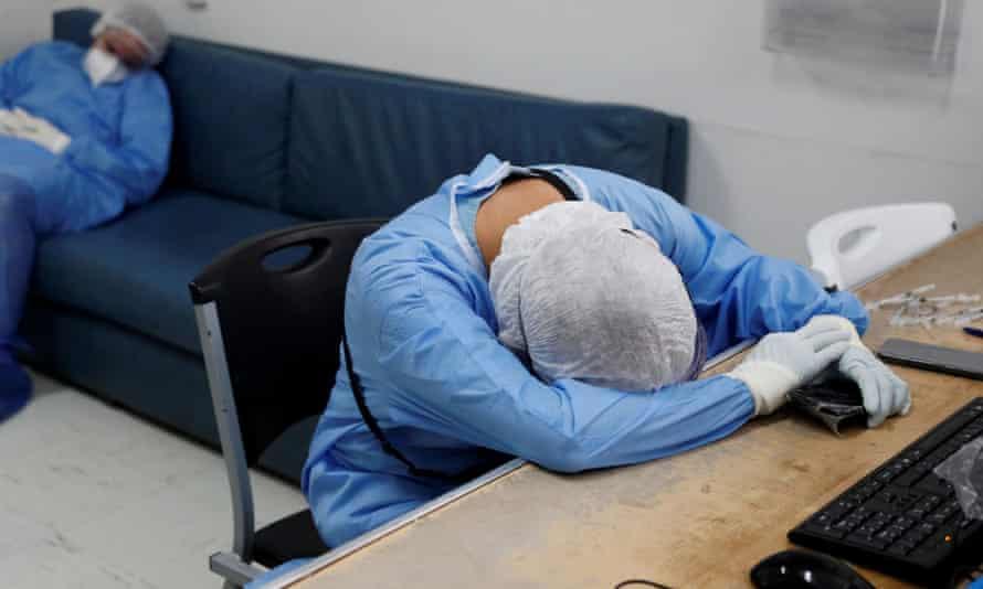 Οι ιατροί με προστατευτικά ενδύματα ξεκουράζονται μετά από ώρες που θεραπεύουν ασθενείς στην Πόλη του Μεξικού, τον Οκτώβριο.