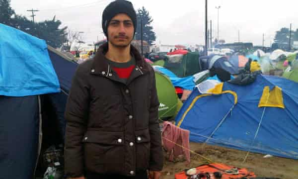 Ayham Hakni standing outside the tent he shares with his mother and three other families at Idomeni.