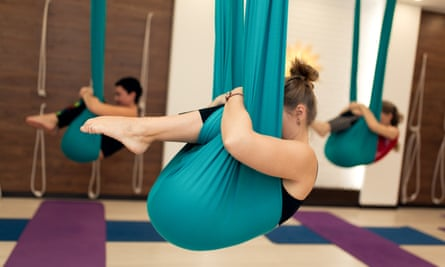 A group of women are hanging in a fetal position in a hammock during an aerial yoga class.