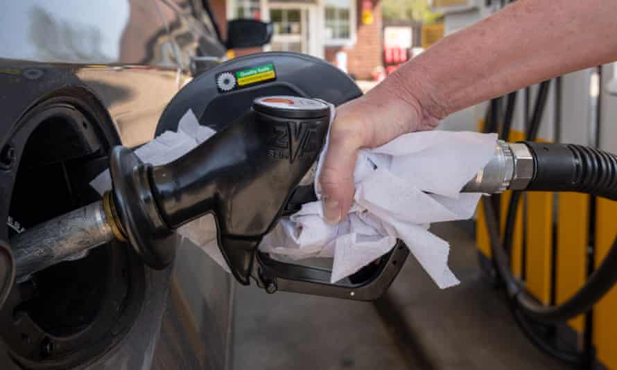 A motorist fills their petrol tank using a paper towel to help prevent the spread of Coronavirus