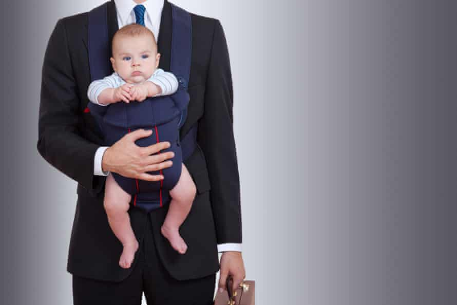Man wearing a suit and carrying a briefcase with baby in carrier strapped to chest