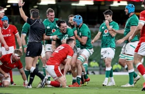 Ireland's James Lowe celebrates with Will Connors and Chris Farrell after scoring their second try.