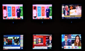Screens show different TV channels giving estimates of general elections as Spain waits for official results in Madrid on April 28, 2019.
