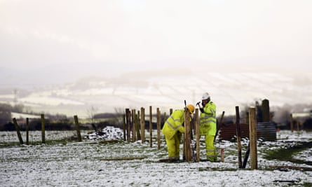Farm workers mend fences near Derry, Northern Ireland.