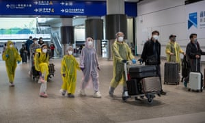 Travellers in full protective gear arriving at Hong Kong international airport.