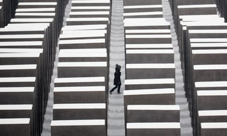 A visitor walks through the snow covered Holocaust memorial in Berlin