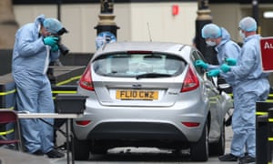 Police forensics officers carry out tests on a silver Ford Fiesta car that was driven into cyclists outside parliament.