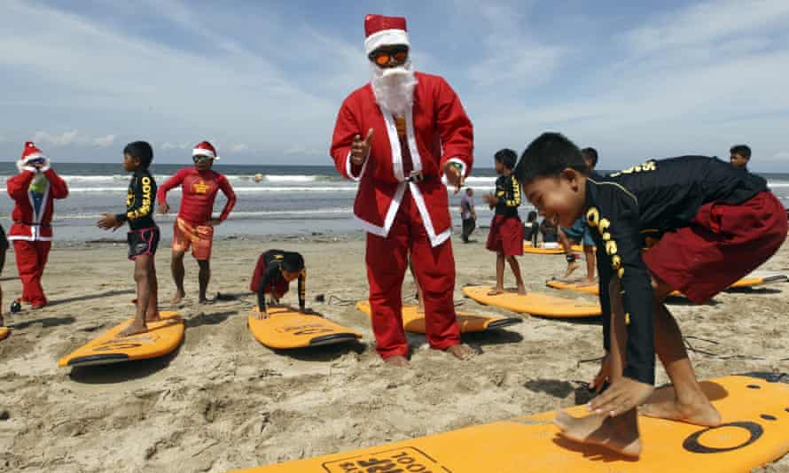 Indonesian surf instructors dressed as Santa Claus teach children how to surf