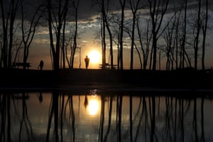 People stand and watch the sun set at Presque Isle State Park in Erie, Pennsylvania