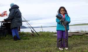 Mary Demientieff Junior, great-granddaughter of an Athabascan elder, holds a silver salmon at their fish camp.