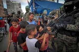 Palestinian boys hold a gun belonging to a member of the Izz ad-Din al-Qassam Brigades in Gaza City