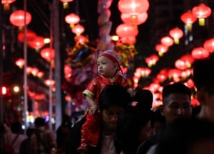 A child sits on a man's shoulder as people take part the celebration on the eve of Chinese Lunar New Year in Yangon, Myanmar
