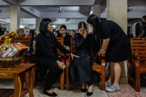 People comfort the mother of Ratchanon Karnchanamethee, a 13-year-old boy, who was killed in the mass shooting at the Terminal 21 shopping mall during his funeral in Korat.