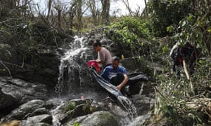 Danalys Luna and Edgardo Feliciano wash their clothes in a stream as people wait for electrical and water grids to be repaired.
